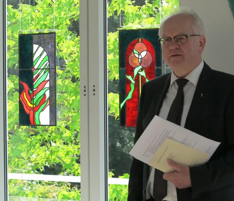 Prof. Meyer zu Schlochtern vor den Glasbildern des Künstlers Burkhard Siemsen