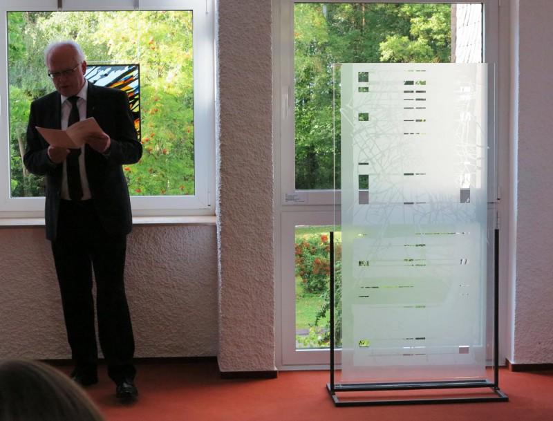 Prof. Meyer zu Schlochtern vor einer Stele des Künstlers Thomas Kuzio (Glasmalerei Peters, Paderborn)